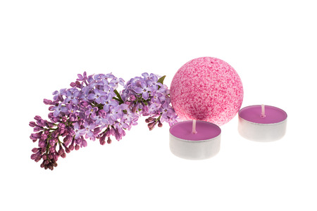 Pink dotted bath bomb, scented candles and spring flowers isolated on white background