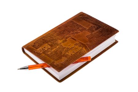 Bruin lederen laptop met oranje balpen geïsoleerd op een witte achtergrond Stockfoto