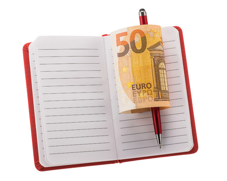 Red open lined blank notebook with ballpoint pen and rolled 50 euro banknote isolated on white background
