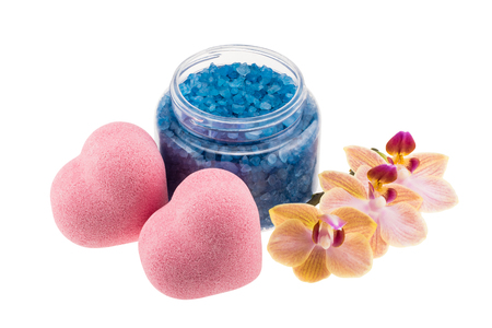 Composition of heart-shaped bath bombs, open bottle with blue sea salt and orchid flower