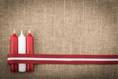 Komposition aus drei roten weißen Kerzen und lettischem Flaggenband