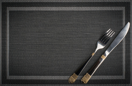 Fork and Knife with golden elements on a placemat, top view with text space