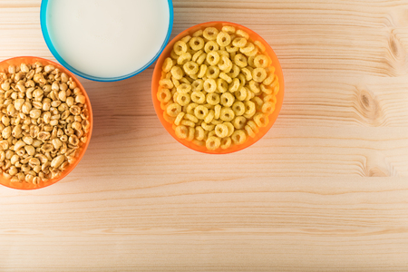 Honey cereals breakfasts and milk in colorful bowls Reklamní fotografie