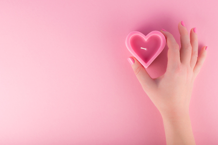 Female hand holding heart shaped pink candle. Valentines day concept