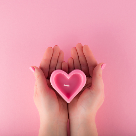 Heart shaped pink candle in female hands
