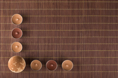 Composition of bath bomb and tea light candles on a bamboo placemat