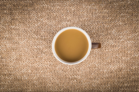 Cup of coffee with milk on knitted background, winter concept, top view