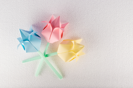 Three origami flowers on white textured background 스톡 콘텐츠