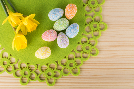 Spring Easter composition of eggs and narcissus flowers on wooden background
