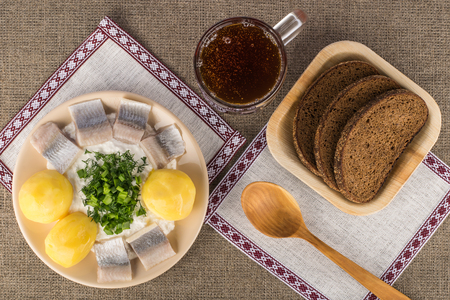 Latvian traditional dish - cottage cheese with boiled potatoes, lightly salted herring and greens