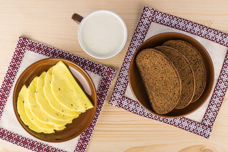 Latvian rye bread and caraway cheese on the national tablecloths