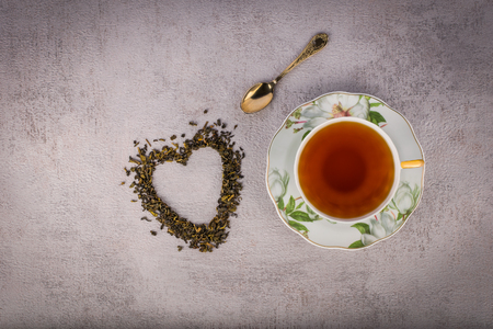 Cup of black tea, small antique spoon and heart-shaped scattered tealeaves