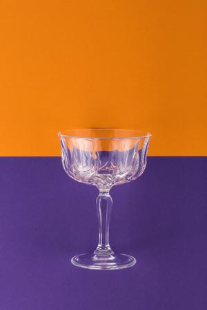 Champagne glass on purple and orange background