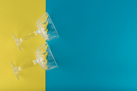 Two champagne glasses on blue and yellow background 스톡 콘텐츠