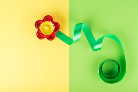 Abstract composition of red glass flower-shaped candlestick and green ribbon. Flower concept
