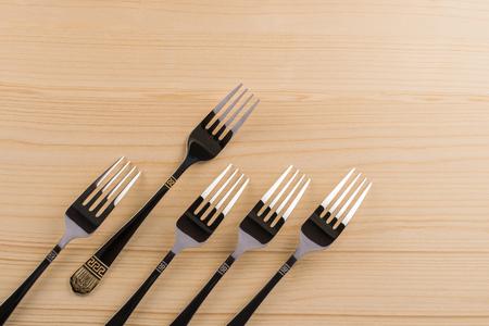 Five steel forks on wooden background