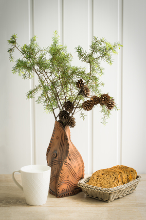 Juniper branch with cones in clay vase, bread basket and cup of milk
