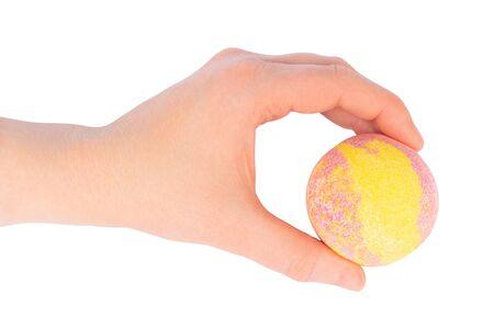 Female hand holding a yellow pink bath ball 스톡 콘텐츠