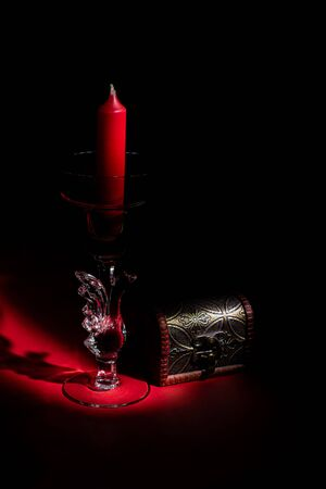 Glass figured candlestick with red candle and small chest, mystery concept