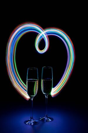 Two glasses of champagne in heart-shaped neon light on a dark background