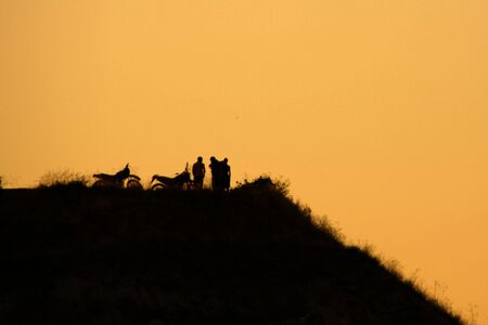 quietness: Silhouette of two motorbikes and bikers on a hill at sunset                  Stock Photo