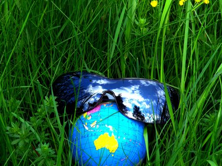 furlough: Globe with sunglasses in a meadow