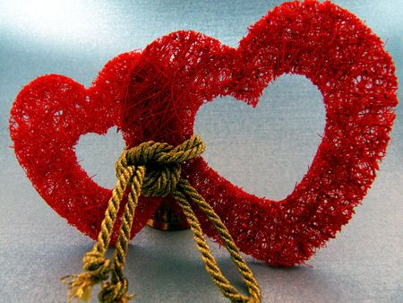 Two red hearts chained with golden cord