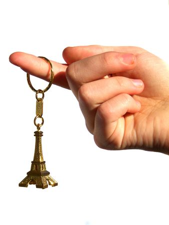 keychain: hand holding the model of the tour eiffel, isolated against white  Stock Photo