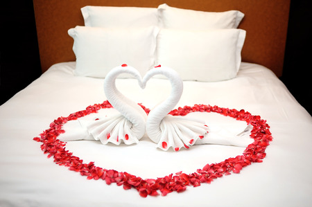 Red rose petals and white pillows on the white bed in wedding 版權商用圖片