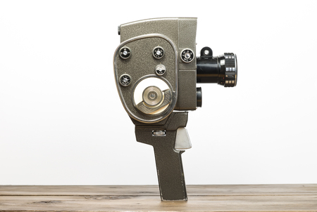 old desk: Old movie camera on a wooden desk Stock Photo
