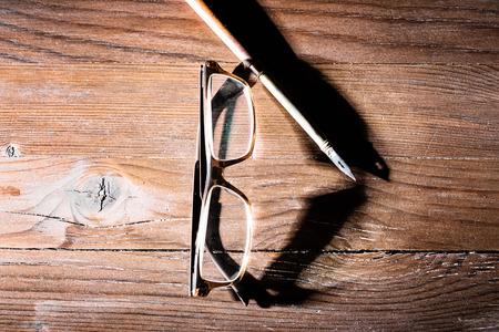 old desk: Old modern glasses with shadow on wooden desk