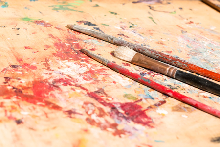 pallette: three old paintbrushes on used artistic pallette Stock Photo