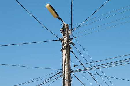 unorganized: Electrical wire on pole. chaotic wire with nest on pole and blue sky background
