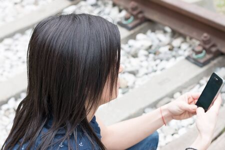 railroad station: Pretty girl texting on phone along the tracks in a railroad station
