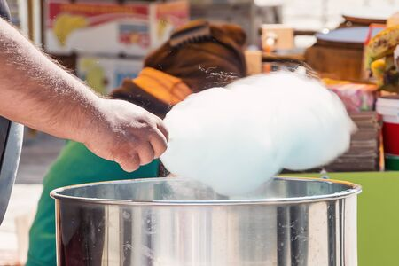 man holding transparent: close up of man makeing cotton candy
