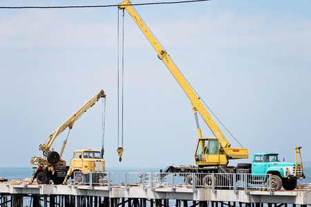 a two wheeled vehicle: Two Old Auto Cranes On The Quay