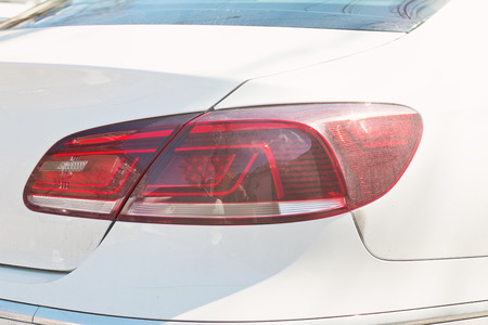 backlights: Car rear lights , red backlights of white powerful sport sedan bodywork, concept Stock Photo