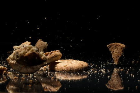 Falling Sweet Cookies On Black Background With Reflection
