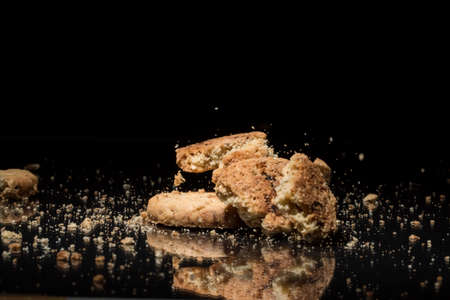 savoury: Falling Sweet Cookies On Black Background With Reflection