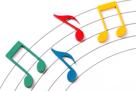 music notation: Color Wooden Musical Notes With Shadows Over Music Sheet