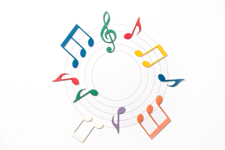 musical notation: Color Wooden Musical Notes With Shadows Over Music Sheet In Circle