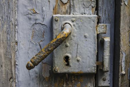 puertas de hierro: Bloqueo viejo en una puerta de madera con la pintura descascarada Foto de archivo