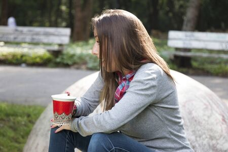 bere caffè: Beautiful young woman with a red cup drinking coffee in a morning park Archivio Fotografico