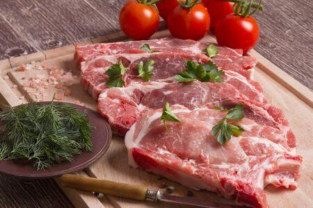 Frisches rohes Schweinekotelettfleisch auf Schneidebrett mit Tomaten, Petersilie und schwarzem Pfeffer