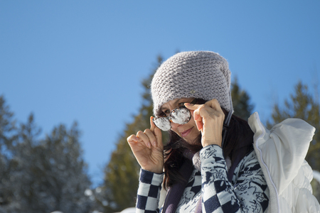 Woman with snowy sunglasses against the blue sky