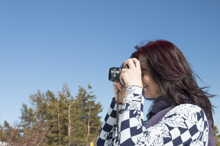 Redhead woman with an old camera in winter against blue sky Reklamní fotografie