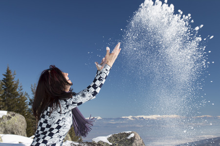 Woman  throwing snow in the air in winter holidays