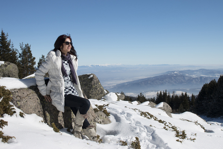 Beautiful woman on a snowy mountain with sunglasses enjoying the blue sky