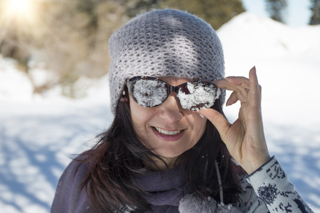 Woman with snowy sunglasses in the winter mountain