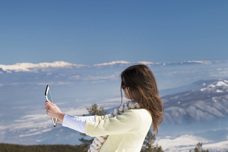 winter photos: Young girl makes selfie photos with a tablet in the mountains in winter